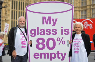Paul Weir with Honor Blackman holding a banner saying 'My Glass is 80% empty'